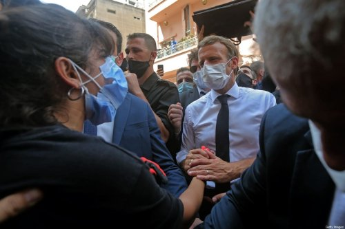 TOPSHOT - French President Emmanuel Macron comforts a Lebanese youth during a visit to the Gemmayzeh neighbourhood, which has suffered extensive damage due to a massive explosion in the Lebanese capital, on August 6, 2020. - French President Emmanuel Macron visited shell-shocked Beirut, pledging support and urging change after a massive explosion devastated the Lebanese capital in a disaster that has sparked grief and fury. (Photo by - / AFP) (Photo by -/AFP via Getty Images)