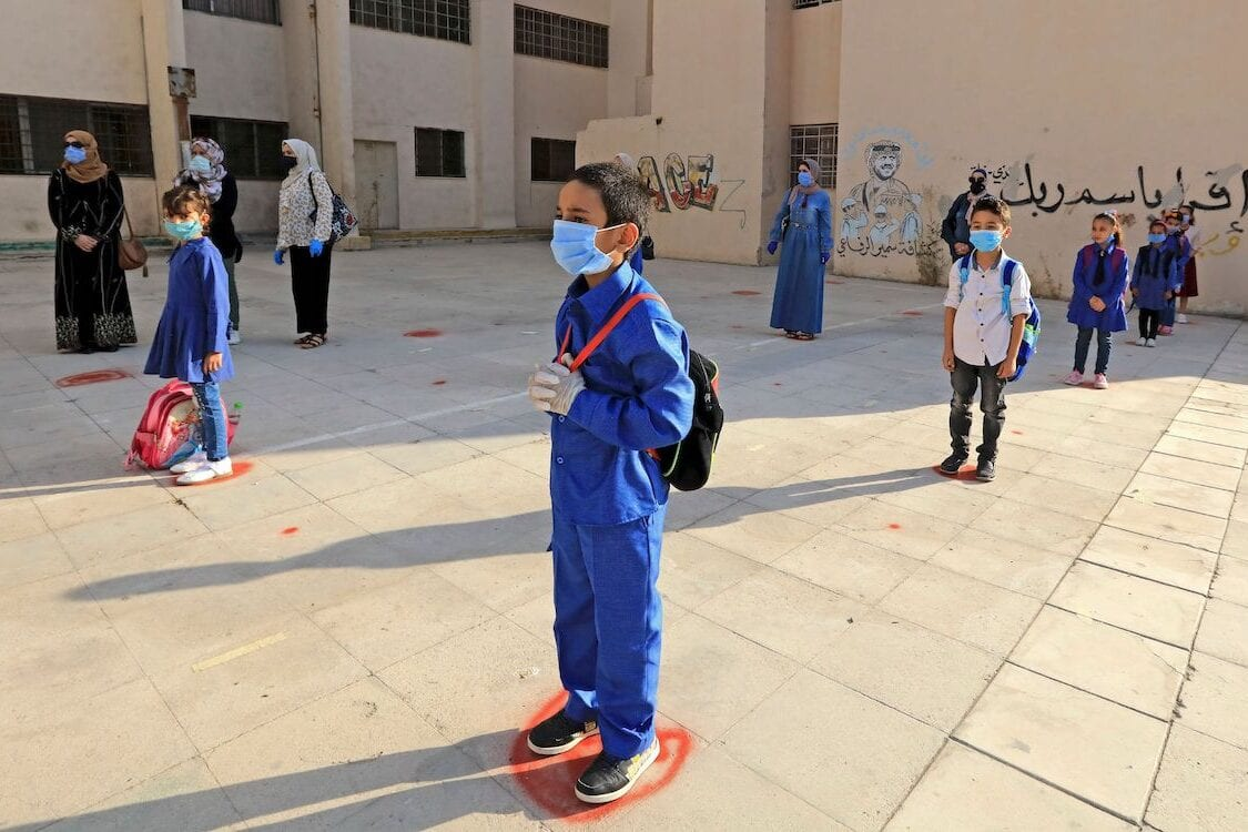 Students, wearing protective masks, wait in line on the first day of school in the Jordanian capital Amman amid the ongoing COVID-19 pandemic, on 1 September 2020. [KHALIL MAZRAAWI/AFP via Getty Images]