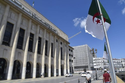 Algerians walk across from the People's National Assembly (parliament) building during a voting session on constitutional reforms in the capital Algiers, on September 10, 2020 [RYAD KRAMDI/AFP via Getty Images]