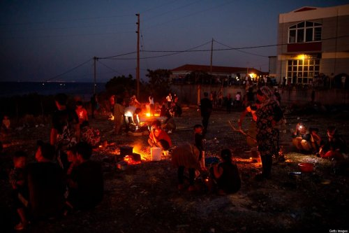 Refugees and migrants from the destroyed Moria camp cook on fire during the early evening on the island of Lesbos, on September 11, 2020. - Greek authorities on September 10 were racing to shelter thousands of asylum seekers left homeless on Lesbos after the island's main migrant camp was gutted by back-to-back fires, which destroyed the official part of the camp housing 4,000 people. Another 8,000 lived in tents and makeshift shacks around the perimeter and many were badly damaged. (Photo by ANGELOS TZORTZINIS / AFP) (Photo by ANGELOS TZORTZINIS/AFP via Getty Images)