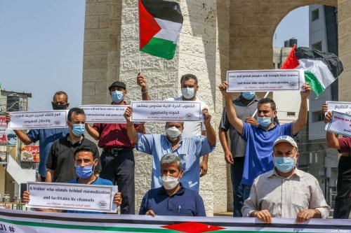 Palestinians carry placards during a protest in Rafah in the southern Gaza Strip, on September 12, 2020 [SAID KHATIB/AFP/Getty Images]