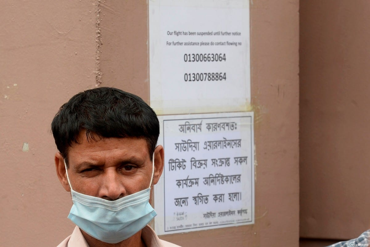 A Bangladeshi migrant worker stands next a notice by Saudi Arabian Airlines as they suspended issuing tickets to Saudi Arabia, in Dhaka on September 22, 2020 [MUNIR UZ ZAMAN/AFP via Getty Images]