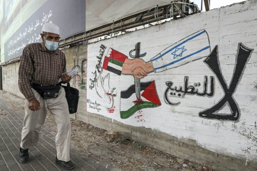 A graffiti depicting hands with sleeves coloured in the UAE and Bahrain flags shaking hands with another with a sleeve bearing the Israeli flag in the West Bank on 4 October 2020 [HAZEM BADER/AFP via Getty Images]
