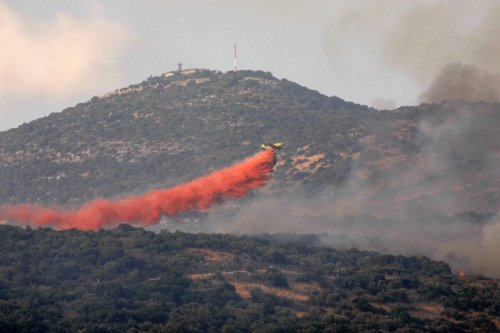 A firefighting plane tries to extinguish a forest fire near the Isralei military base of Har Dov on Mount Hermon, a strategic and fortified outpost at the crossroads between Israel, Lebanon, and Syria, on October 10, 2020. (Photo by JALAA MAREY / AFP) (Photo by JALAA MAREY/AFP via Getty Images)