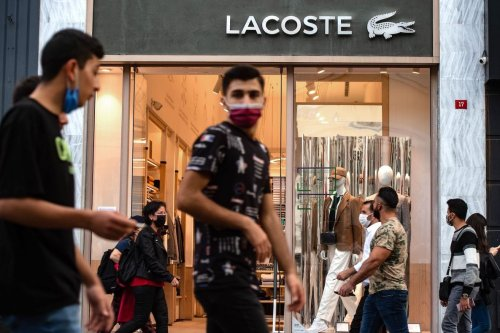 "People, wearing face masks, walk in front of a French brand shop ""Lacoste"" in Istanbul, on 26 October 2020. [YASIN AKGUL/AFP via Getty Images]"