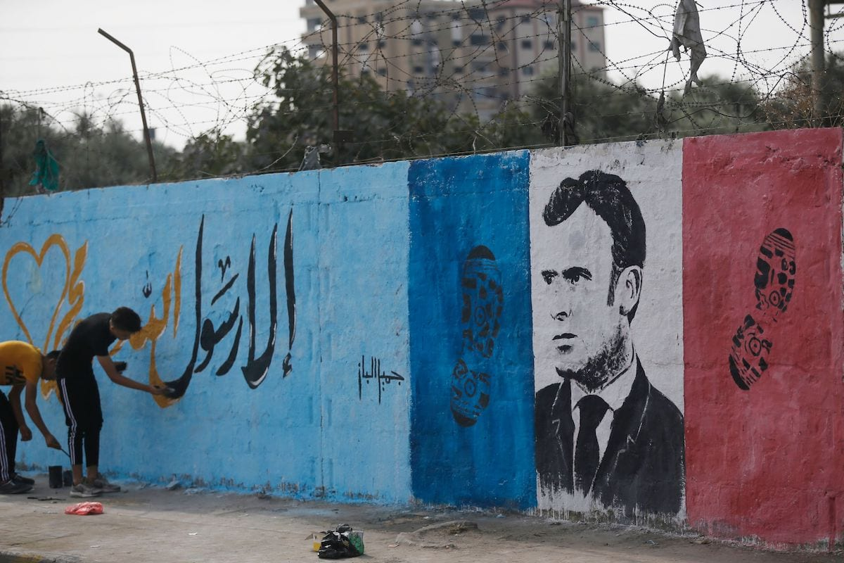 """Palestinian artists write in arabic """"Anyone but the Prophet"""" as they draw a mural bearing the portrait French President Emmanuel Macron in the Nusseirat refugee camp in the central Gaza Strip on 28 October 2020, as they denounce Macron's defence of cartoons depicting the Prophet Mohammed. [MOHAMMED ABED/AFP via Getty Images]"""