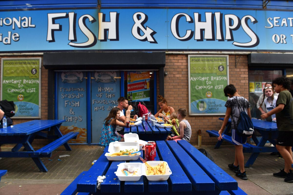 BLACKPOOL, ENGLAND - JULY 31: People enjoy fish and chips on July 31, 2020 in Blackpool, England. High temperatures are forecast across the UK today, with some areas in the south expected to reach 33-34C. (Photo by Anthony Devlin/Getty Images)