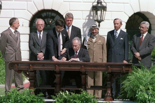 Israeli Foreign Minister Shimon Peres (C) signs the historic Israel-PLO Oslo Accords on Palestinian autonomy in the occupied territories on September 13, 1993 in a ceremony at the White House in Washington, D.C. [J. DAVID AKE/AFP via Getty Images]