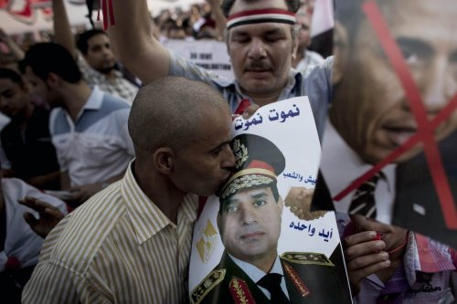 An Egyptian man kisses a picture of General Abdel Fattah al-Sisi in a pro-Sisi protest in Tahrir Square on July 7, 2013 in Cairo, Egypt. [Carsten Koall/Getty Images]