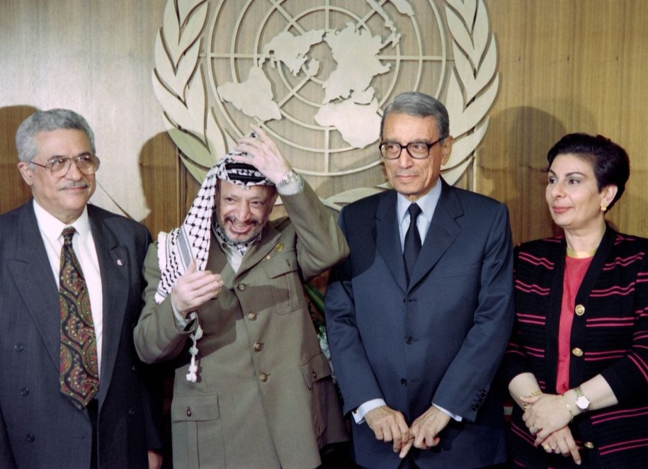 Palestinian Liberation Organization chairman Yasser Arafat (2nd L) adjusts his kaffiyeh on September 14, 1993 as he poses for photos with U.N. Secretary General Boutros Boutros-Ghali (2nd R), PLO political director Mahmoud Abbas (L) and PLO spokeswoman Hanan Ashrawi (R), at United Nations headquarters, one day after the signing of the historic Israel-PLO Oslo Accords. [HAI DO/AFP via Getty Images]