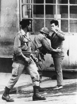 French soldiers search a civilian in an Algiers street, during the Algerian War of Independence [Central Press/Getty Images]