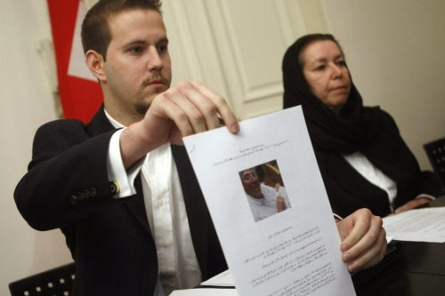 "US Daniel Levinson (L) shows a picture of his father, ex-FBI agent Robert Levinson, holding his grandson Ryan during a press conference with his mother Christine at the Swiss embassy in Tehran, 22 December 2007. The wife of the former agent missing in Iran since March said today she has received ""no answers"" about his fate at the end of her trip to the Islamic republic in search of her husband, who Washington says went missing on a visit to the Iranian island of Kish. The Tehran government reiterated earlier it has no information that Levinson had disappeared on its territory. AFP PHOTO/BEHROUZ MEHRI (Photo credit should read BEHROUZ MEHRI/AFP via Getty Images)"