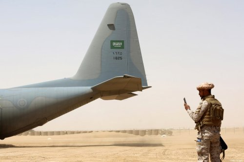 A Saudi soldier stands guard before aid supplies are unloaded from a Saudi air force cargo plane at an airfield in Yemen's central province of Marib, on March 12, 2018 [ABDULLAH AL-QADRY/AFP via Getty Images]