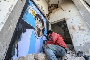 A graffiti artist Syrian Aziz Esmer draws a portrait of Diego Armando Maradona on the walls of a home destroyed after the attacks of Assad regime forces, in Idlib, Syria on November 27, 2020. [İzzeddin idilbi - Anadolu Agency]