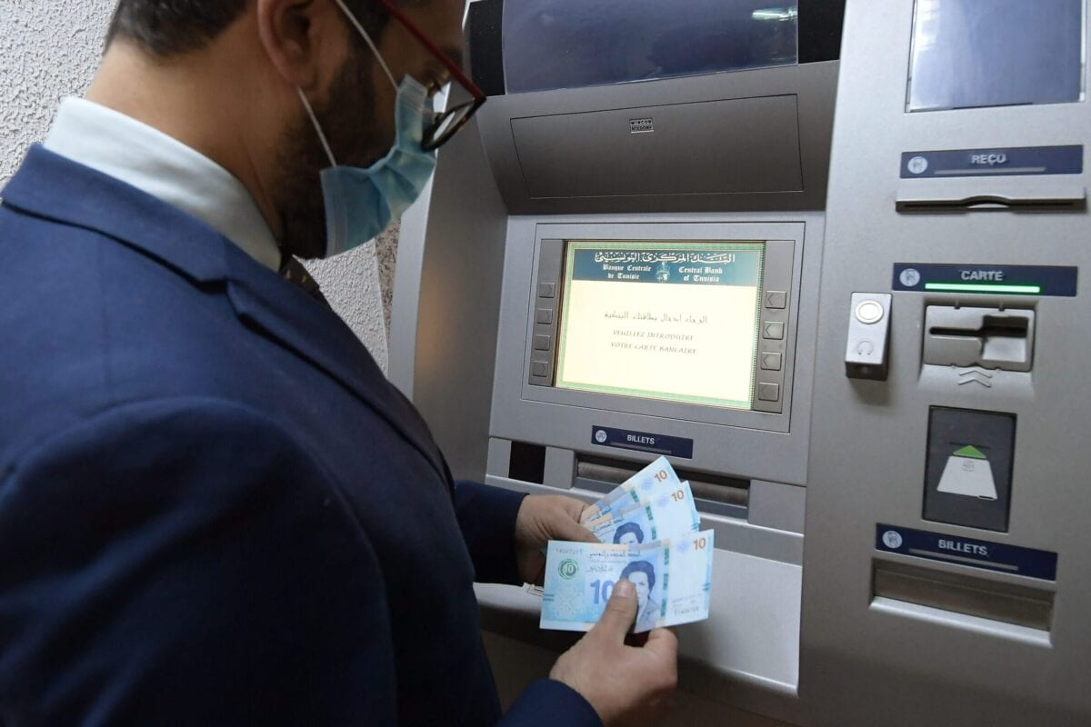 A man retrieves newly circulating Tunisian bank notes from an ATM in the capital Tunis, on March 27, 2020 [FETHI BELAID/AFP via Getty Images]