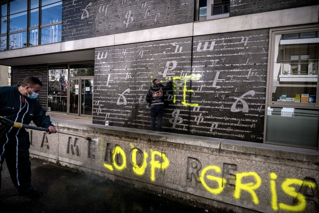 """Men clean an outside wall of the National Armenian Memorial, near Lyon, on November 1, 2020 where pro-Turkish yellow letters graffiti tags have been painted overnight. - Inscriptions read """"RTE"""" which can refers to Turkish Prime minister Recep Tayyip Erdogan and """"Grey Wolf"""" (Loup Gris), the name of an ultra-nationalist movement in Turkey [JEFF PACHOUD/AFP via Getty Images]"""