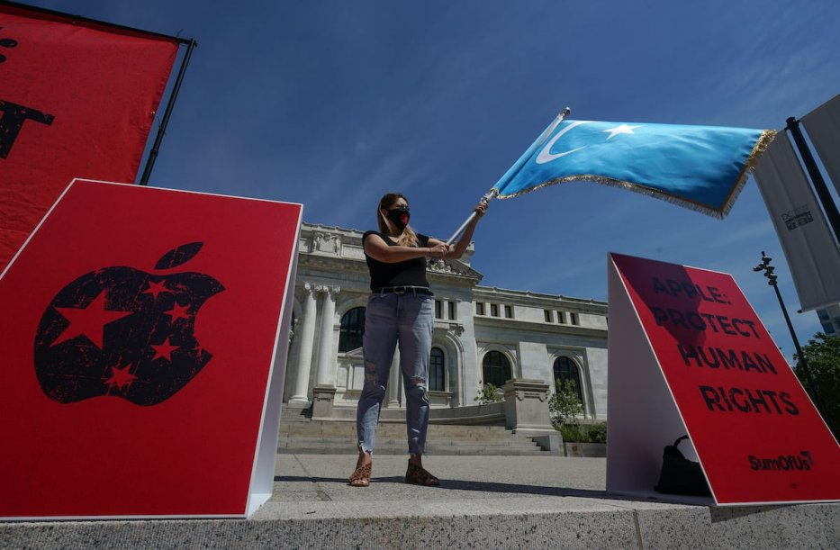 Activist waves a flag of the Uyghur region as she takes part in a protest outside of the Apple Store on July 30, 2020 in Washington, DC [Jemal Countess/Getty Images for SumOfUs]