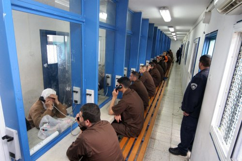 GILBOA PRISON, Israel: Palestinian men sit in their brown prison uniforms behind glass talking on phones to relatives 05 March 2006 at the Gilboa prison, east of the northern Israeli town of Afula. Most of the 850 adult male prisoners in this prison are serving very long jail terms and some are serving life sentences. PHOTO/Hagai AHARON-ISRAEL OUT (Photo credit should read HAGAI AHARON/AFP via Getty Images)
