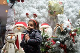 A child poses in front of a Christmas-themed window display in a neighbourhood with a large Christian population in Tehran, Iran, on December 22, 2020 [Fatemeh Bahrami / Anadolu Agency]
