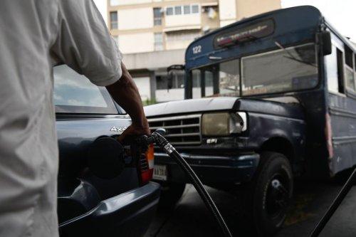 A Petroleos de Venezuela SA (PDVSA) worker pumps gas in a car in Caracas, on 21 May 2019. [MARVIN RECINOS/AFP via Getty Images]