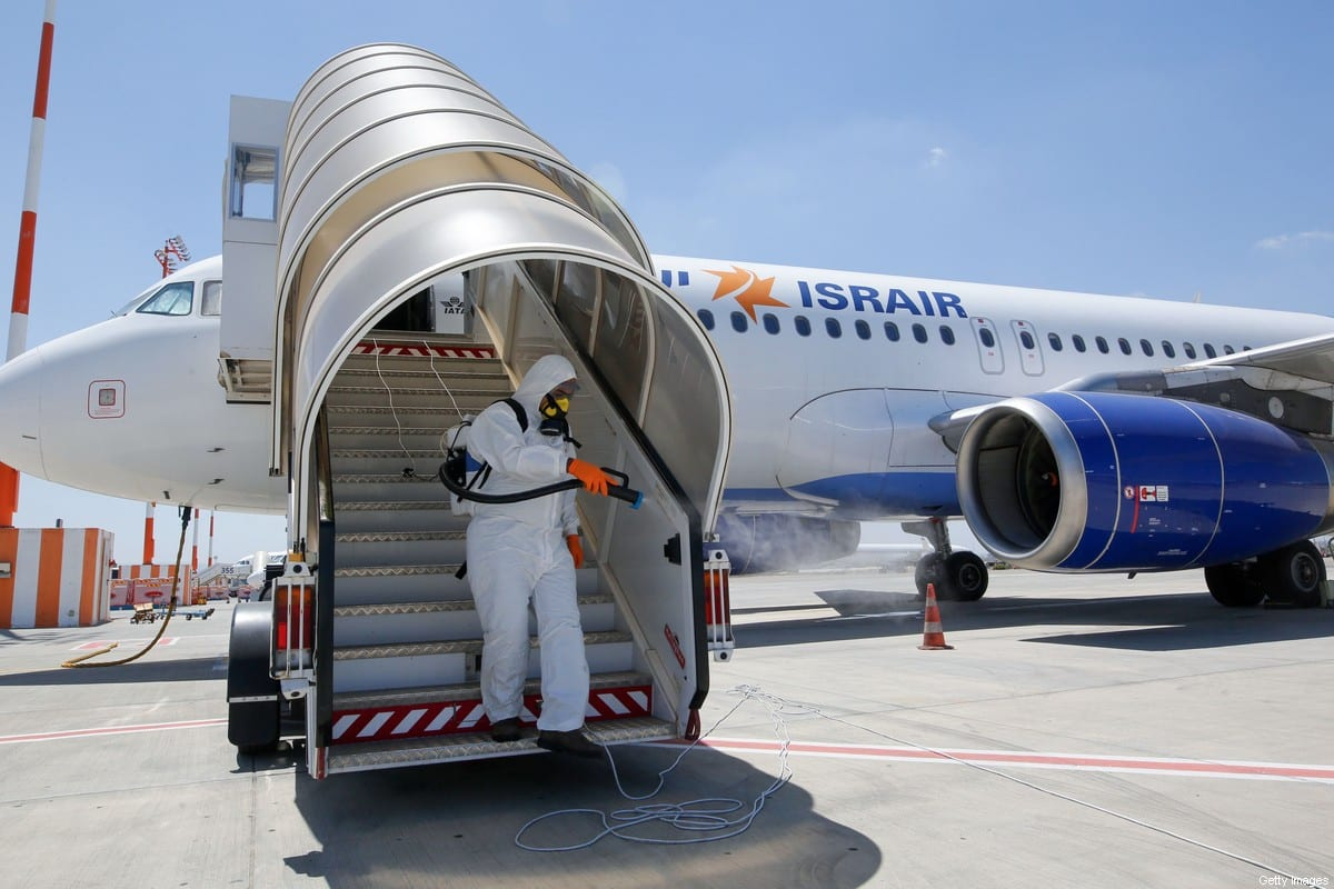 An Israeli worker in full hazmat suit sprays disinfectant on the boarding stairs of an Israir Airlines Airbus A320 airplane, at the Ben Gurion International Airport near the central Israeli city of Tel Aviv, on June 14, 2020, amid the novel coronavirus pandemic. (Photo by GIL COHEN-MAGEN / AFP) (Photo by GIL COHEN-MAGEN/AFP via Getty Images)