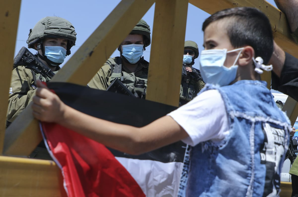 Israeli security forces look at a Palestinian boy lifting a national flag during a rally to protest Israel's plan to annex parts of the occupied West Bank, in the village of Haris, southwest of Nablus, on 28 August 2020. [JAAFAR ASHTIYEH/AFP via Getty Images]