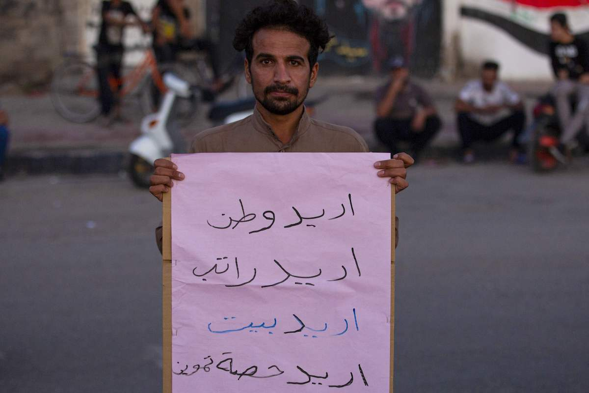 """An Iraqi protester carries a placard which reads in Arabic """"I want a homeland, I want a salary, I want a home, I want a share of provisions"""" during an anti-government demonstration in the southern city of Basra on 13 November 2020. [HUSSEIN FALEH/AFP via Getty Images]"""