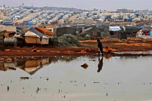 A Syrian woman walks on a flooded patch at a camp for displaced Syrians near the town of Kafr Lusin by the border with Turkey, in Syria's rebel-held northwestern province of Idlib on December 15, 2020. [AAREF WATAD/AFP via Getty Images]
