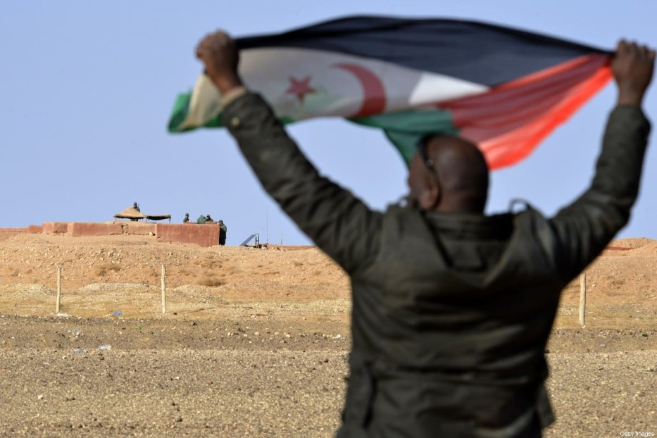 A Saharawi man holds up a Polisario Front flag in the Al-Mahbes area near Moroccan soldiers guarding the wall separating the Polisario controlled Western Sahara from Morocco on 3 February 2017. [STRINGER/AFP via Getty Images]