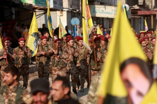 Kurdish People's Protection Units (YPG) military police members demonstrate with their flags and others bearing the portrait of Kurdistan Worker's Party (PKK) leader Abdullah Ocalan in the Kurdish town of Al-Muabbadah in the northeastern part of Hassakah province on February 24, 2018, denouncing the Turkish military operation against YPG forces in the northwestern Kurdish enclave of Afrin [DELIL SOULEIMAN/AFP via Getty Images]
