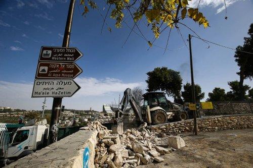 The Israeli-run Jerusalem Municipality team along with Israeli soldiers and bulldozers demolish part of the Al Yousifieh Cemetery in Jerusalem on 14 December 2020 [Mostafa Alkharouf/Anadolu Agency]