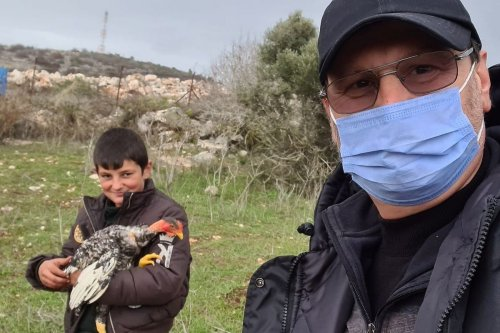 Nine-year-old Hussein Chartouni can be seen with a chicken given as a gift after his chicken was taken by the Israeli forces