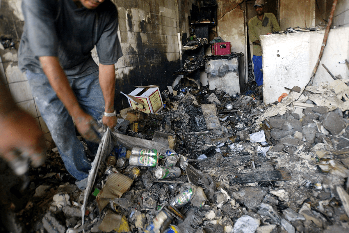 Employees clean the rubbish at an alcohol store that was hit by a bomb in Baghdad [KARIM SAHIB/AFP via Getty Images]