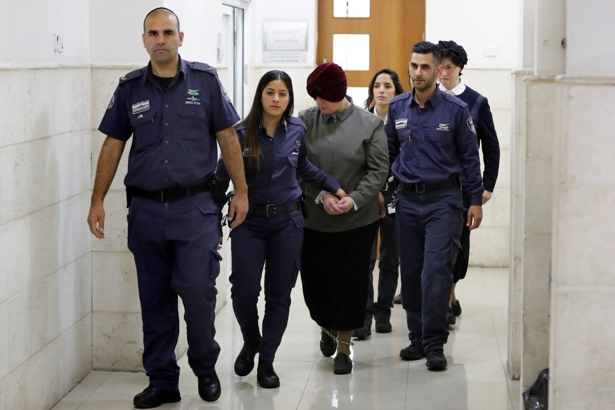 Malka Leifer (C), a former Australian teacher accused of dozens of cases of sexual abuse of girls at a school, is escorted by police as she arrives for a hearing at the District Court in Jerusalem on February 27, 2018 [AHMAD GHARABLI/AFP via Getty Images]