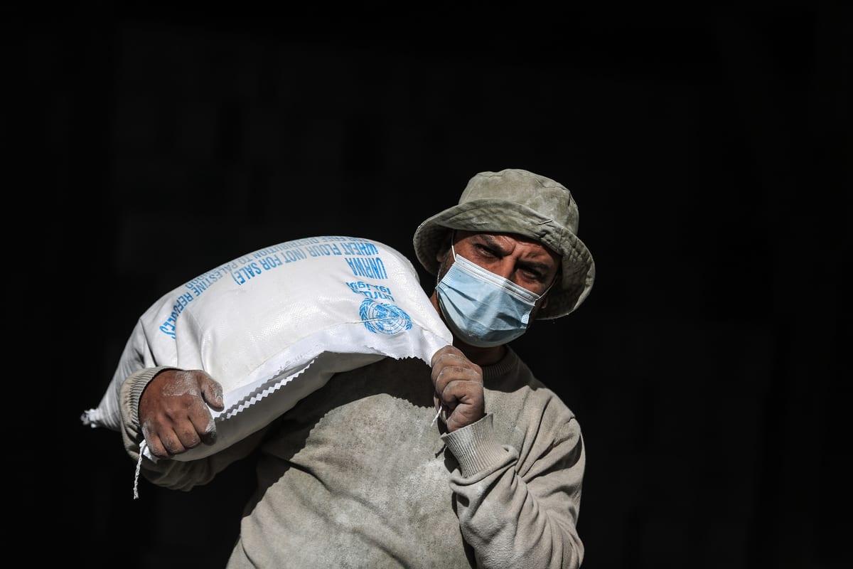 Workers of United Nations Palestine Refugee Agency (UNRWA) prepare aids distribute to Palestinian refugees in Al-Shati Camp in Gaza City, Gaza on 14 January 2020. [Ali Jadallah - Anadolu Agency]