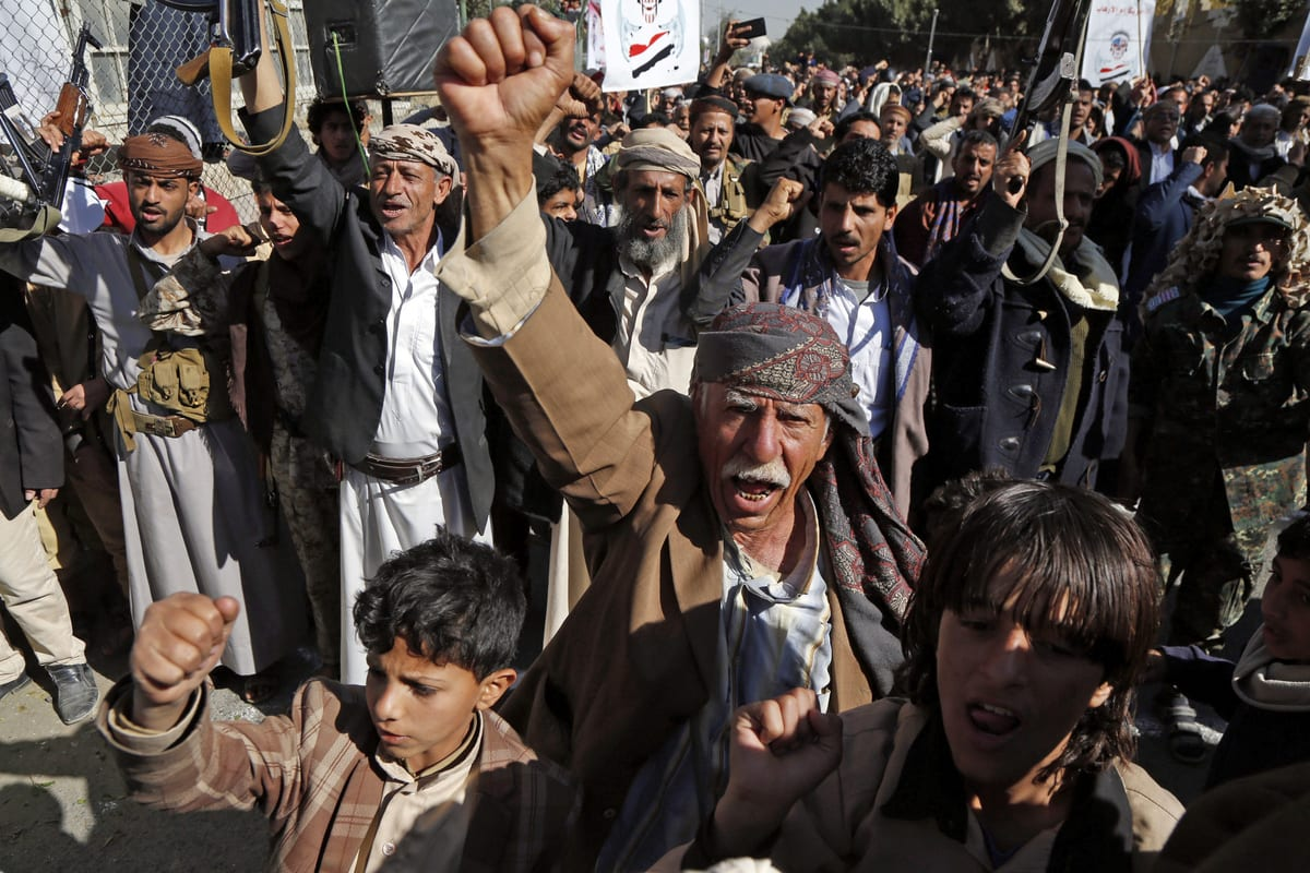 """SANAA, YEMEN - JANUARY 18: Supporters of Yemen's Huthi movement raise their fists up as they chant slogans during a demonstration in front of the closed US Embassy in the capital Sanaa on January 18, 2021, to reject outgoing US President Donald Trump's decision to designate the Huthi group a """"foreign terrorist organisation"""". - Impoverished Yemen is mired in a devastating conflict between Iran-backed Huthi rebels and government forces backed by Saudi Arabia that has left tens of thousands dead and sparked a dire humanitarian crisis. ( Mohammed Hamoud - Anadolu Agency )"""