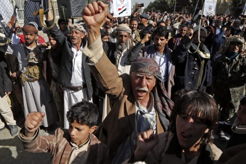"SANAA, YEMEN - JANUARY 18: Supporters of Yemen's Huthi movement raise their fists up as they chant slogans during a demonstration in front of the closed US Embassy in the capital Sanaa on January 18, 2021, to reject outgoing US President Donald Trump's decision to designate the Huthi group a ""foreign terrorist organisation"". - Impoverished Yemen is mired in a devastating conflict between Iran-backed Huthi rebels and government forces backed by Saudi Arabia that has left tens of thousands dead and sparked a dire humanitarian crisis. ( Mohammed Hamoud - Anadolu Agency )"