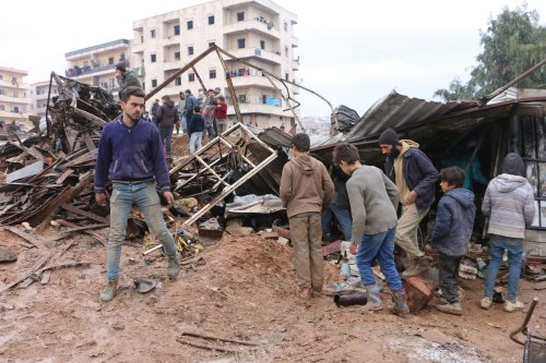 People inspect the damaged site after a bomb-laden vehicle exploded in northern Syria's Afrin on January 30, 2021 [Hişam El Homsi/Anadolu Agency]