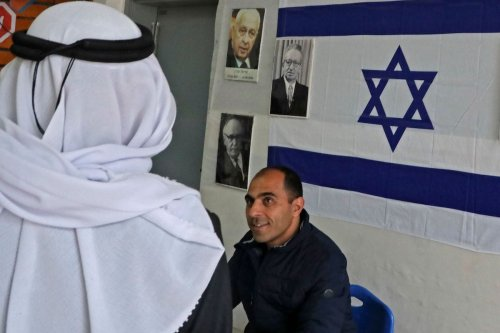 An Arab-Israeli man arrives at a poling station, decorated with portraits of Israeli politicians, to cast his ballot for the parliamentary election in the Bedouin town of Rahat near the southern Israeli city of Beersheba on 2 March 2020. [HAZEM BADER/AFP via Getty Images]