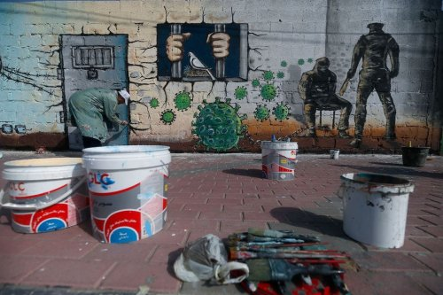 A Palestinian artist paints a mural in a show of support for Palestinian prisoners held in Israeli jails amid the COVID-19 pandemic, in Gaza City on April 20, 2020 [MOHAMMED ABED/AFP via Getty Images]