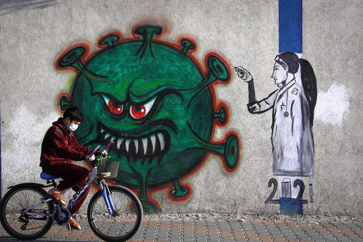 A Palestinian youth wearing a face mask rides his bicycle past a mural painting of a nurse injecting a vaccine to a COVID-19 virus in Gaza City, on 31 December 2020. [MOHAMMED ABED/AFP via Getty Images]