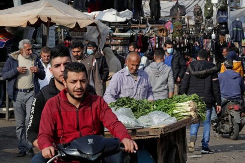 Lebanese, some wearing protective masks due to the COVID-19 pandemic, shop at a market in the Sabra neighbourhood of Beirut on 6 January 2021. [ANWAR AMRO/AFP via Getty Images]