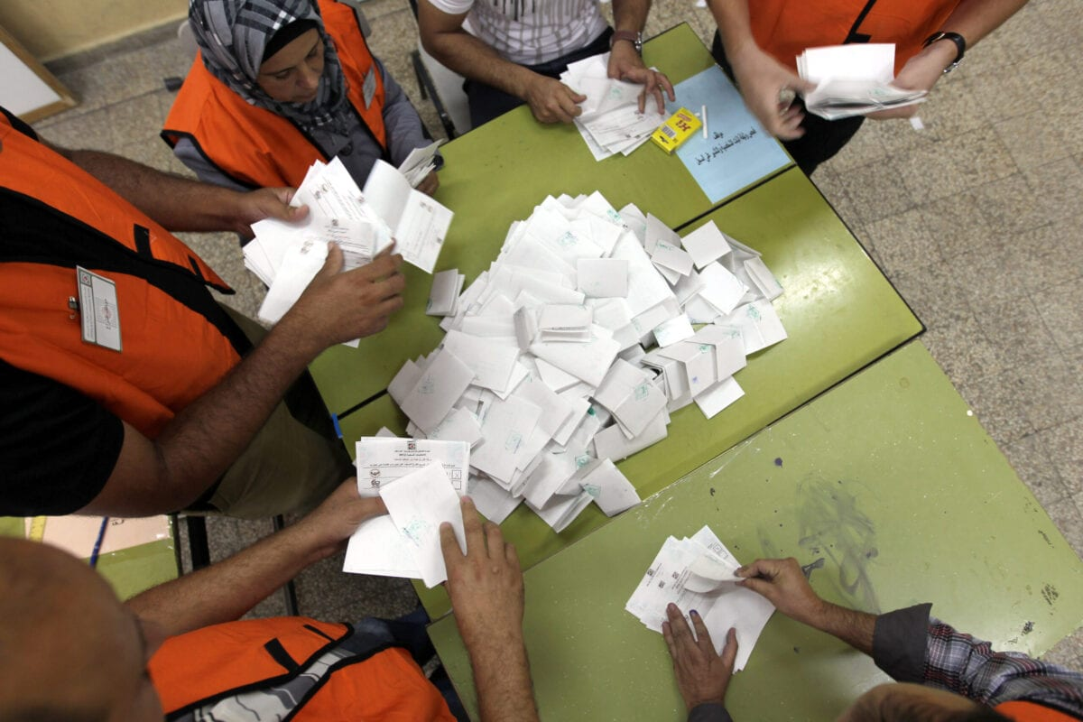 Electoral employees sort out ballot papers after polling stations closed in the northern West Bank village of Deir al-Hatab on October 20, 2012. Polling stations were closed in the West Bank after 12 hours of voting in the first Palestinian election since 2006, with voters casting their ballots in a municipal poll that was boycotted by Hamas. AFP PHOTO/JAAFAR ASHTIYEH (Photo credit should read JAAFAR ASHTIYEH/AFP via Getty Images)