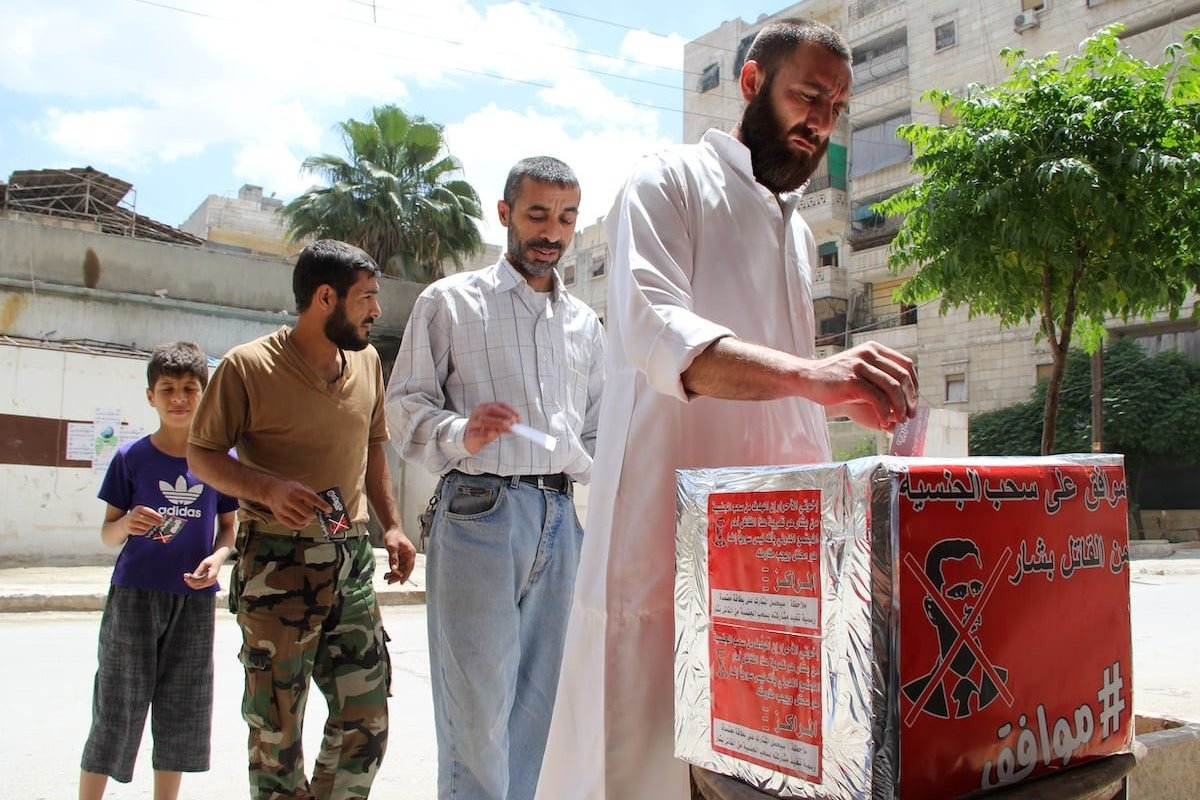 """Syrian men pretend they are casting their votes during a mock election calling for the """"criminal"""" Syrian President Bashar al-Assad to the stripped of his Syrian nationality, on 3 June 2014 in the mostly rebel-held city of Aleppo. [BARAA AL-HALABI/AFP via Getty Images]"""