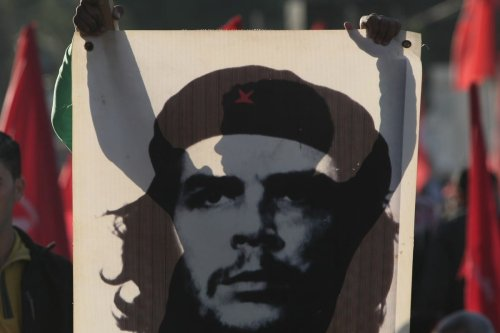 A Palestinian supporter of the Popular Front for the Liberation of Palestine (PLFP) holds up a portrait of Mohammed Mahmoud Musleh Al-Aswad — 'Guevara of Gaza' during a rally in Gaza on 11 December 2011 [MAHMUD HAMS/AFP/Getty Images]