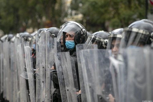Police officers block the road as people stage a demonstration demanding the release of detainees arrested in a protest held against the coronavirus (Covid-19) pandemic lockdown, at Habib Burgiba street in Tunis, Tunisia on 23 January 2021. [Yassine Gaidi - Anadolu Agency]
