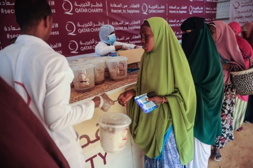 Somali internally displaced people receive food distribution from a Qatari charity in Mogadishu, Somalia, on May 22, 2018 [MOHAMED ABDIWAHAB/AFP via Getty Images]