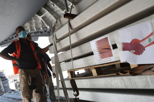 Workers load a plane as Qatar begins sending field hospitals and medical aid to Lebanon from the al-Udeid airbase on August 5, 2020 [KARIM JAAFAR/AFP via Getty Images]