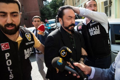 Turkish police officers escort televangelist and leader of a sect, Adnan Oktar (C) on July 11, 2018, in Istanbul [AFP via Getty Images]