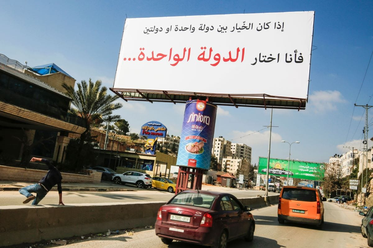 "A picture taken on February 23, 2017 shows a billboard, of unknown origin, on a main road leading to the West Bank city of Ramallah, reading in Arabic: ""If the choice is between one state or two states, then I am choosing the one state."" [ABBAS MOMANI/AFP via Getty Images]"